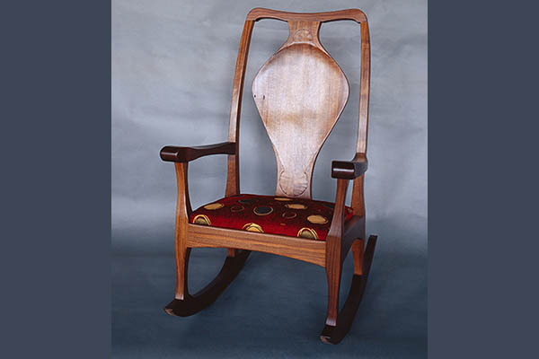 "Walnut rocker: Sculptured arms and legs. 43″ h x 22 "" w x 19 "" d"